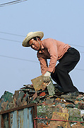 A junk yard worker sorts motherboards of old computers in Guiyu, China March 8, 2005. For years, developed countries have been exporting tons of electronic waste to China for inexpensive, labor-intensive recycling and disposal.