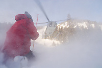A helicopter lifts off above the ski guides at High Mountain Heli Skiing in Jackson Hole, Wyoming.