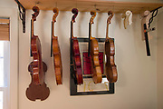 A the workshop of Boston violin maker Christopher White, instruments are displayed in various states of repair and/or finishing.