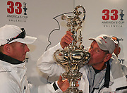 Larry Ellison kisses the America's Cup.during the Pressconference.Helmsman James Spithill on the left..BMW Oracle wins the America's Cup.2010 America's Cup, Valencia.©2010 Kaufmann/Forster go4image.com