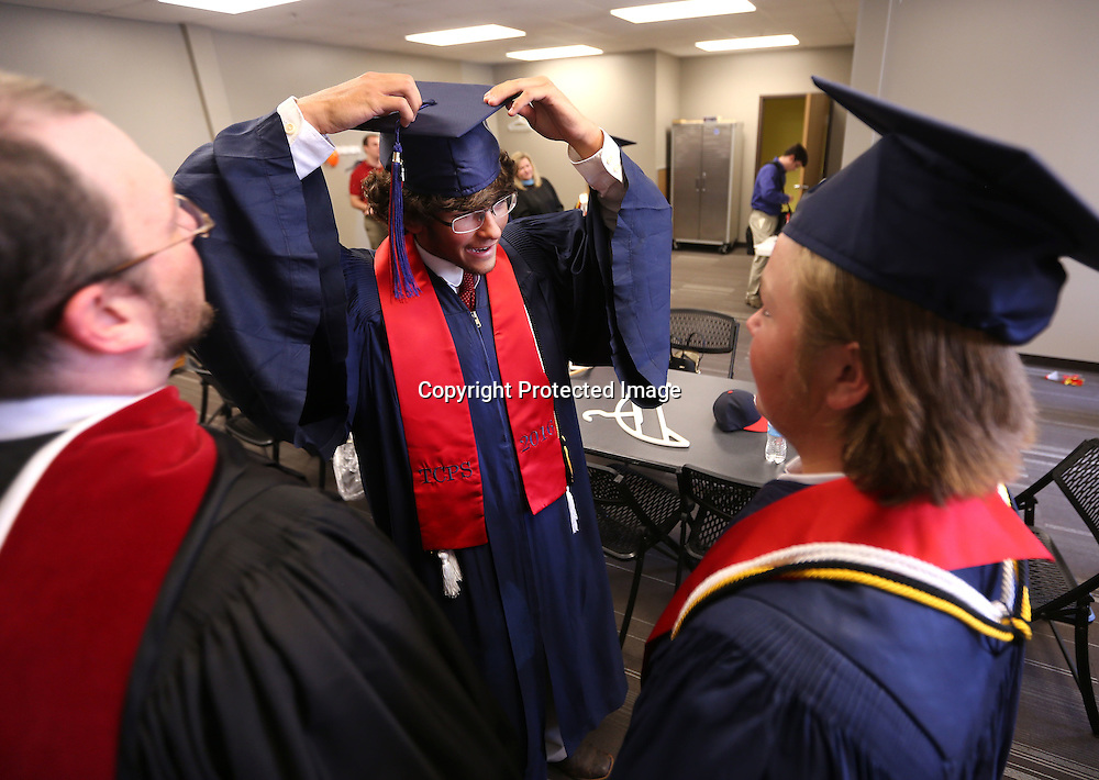 Adam Robison | BUT AT PHOTOS.DJOURNAL.COM<br /> Austin Laney, center, stands with TCPS faculty member James Underwood, left, and fellow classmate Lucas Hartigan, as he adjusts his cap while getting ready for their graduation ceremony that was held at the Orchard in Tupelo Saturday.