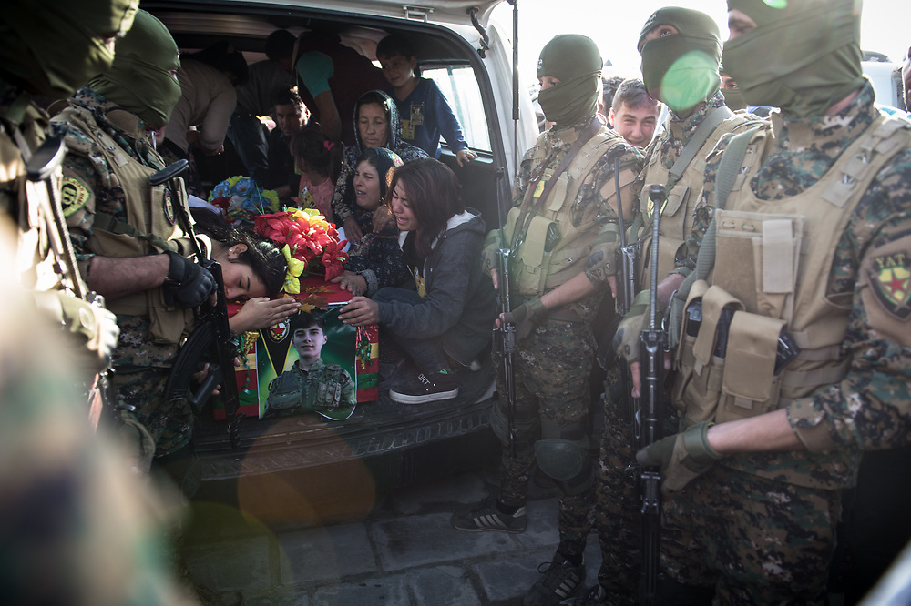 At Kobane's Martyrs Cemetery, friends and relatives mourn by the coffin of a YPG fighter killed during the Raqqa operation. Kobanê, October 14, 2017