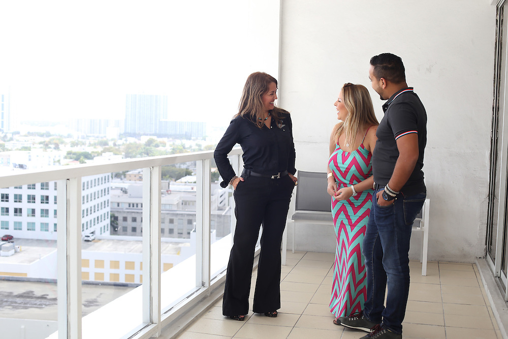 4/13/14----Miami Beach, Florida---Photo by Angel Valentin<br /> Miami realtor Maritza Cuellar, center in black, talks to Joanthan Blanco and Desiree Leon an apartment the Venezuelan couple just rented from her for $4,000 a month in Miami Beach's Decoplage Condominium on Lincoln Road.