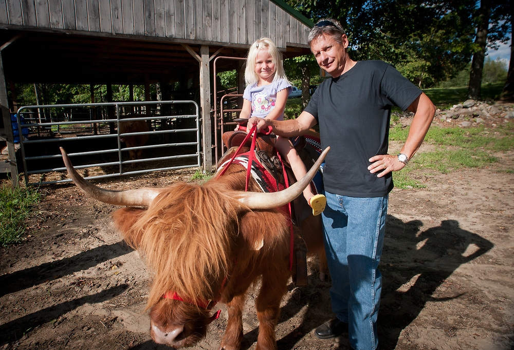 Presidential hopeful, former New Mexico Governor Gary Johnson poses with Mariah McKim as she sits on Missy a Scottish Highlander as he pays a visit and takes a tour of Miles Smith farm in Loudon, NH. 23rd of august 2011.