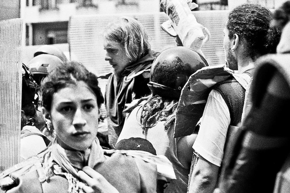 Genova, venerdì 20 luglio 2001. Giornata delle piazze tematiche. Corteo della disobbedienza civile. Lo sguardo smarrito di una manifestante. Il corteo parte in ritardo rispetto ai programmi. Notizie preoccupanti che arrivano dalle altre manifestazioni,  assaltate da gruppi di casseurs (il cosiddetto Black Block) e dalle forze di polizia.