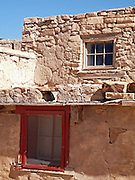 Details of adobe pueblo construction show how wood-framed windows are set into the stone-and-plastered walls of the houses atop the mesa on which Acoma Pueblo people built their Sky City hundreds of years ago.  Some Acoma families still occupy such houses year round while others use their Sky City homes only during feast days and other celebrations and ceremonies.