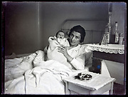 mother with new born baby in bed France, circa 1930s