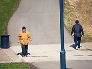 "29 MARCH 2020 - DES MOINES, IOWA: People social distance while they walk on a paved trail near downtown Des Moines. On Sunday morning, 29 March, Iowa reported 336 confirmed cases of the Novel Coronavirus (SARS-CoV-2) and COVID-19. There have been four deaths attributed to COVID-19 in Iowa. Restaurants, bars, movie theaters, places that draw crowds are closed until 07 April. The Governor has not ordered ""shelter in place""  but several Mayors, including the Mayor of Des Moines, have asked residents to stay in their homes for all but the essential needs. People are being encouraged to practice ""social distancing"" and many businesses are requiring or encouraging employees to telecommute.         PHOTO BY JACK KURTZ"