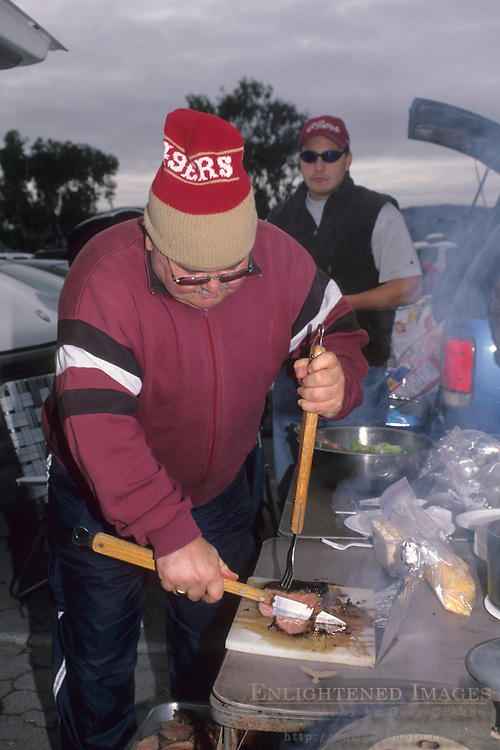 San Francisco 49'ers Footbal fan cooking meat at a tailgate party, San Francisco, California