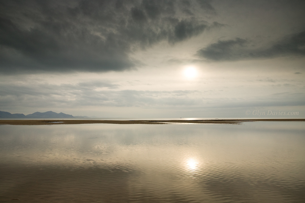 Calm seas at Llanddwyn Beach West Anglesey, Wales, and a sand bar revealed at low tide.