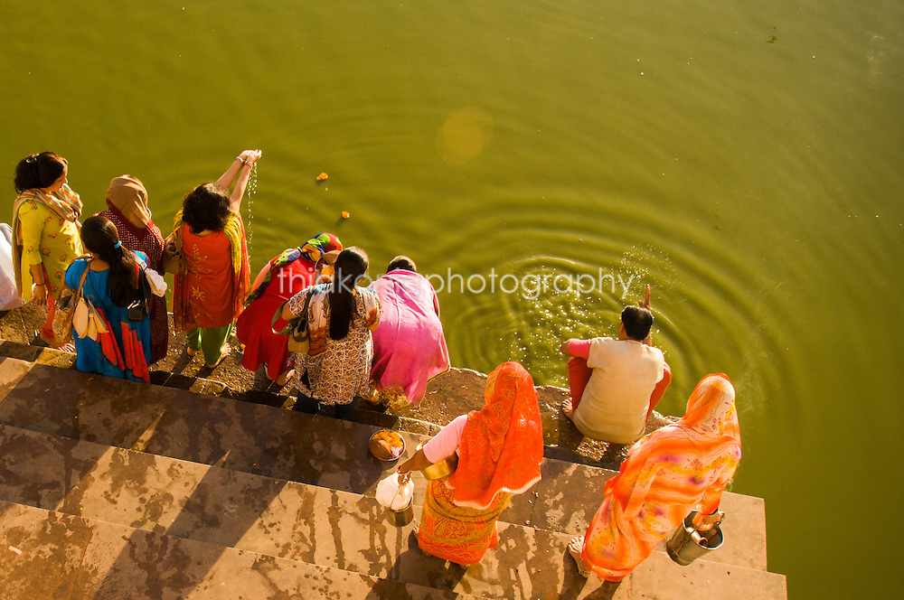 Pilgrims reach the holy water of Pushkar Lake in Rajashan, India. The people's colorful clothes contrasts against the green water of the lake.
