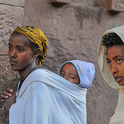 Woman with a baby on her back and a young girl attend a ceremony in one of the rock hewn churches of Lalibela, Lalibela, Ethiopia.