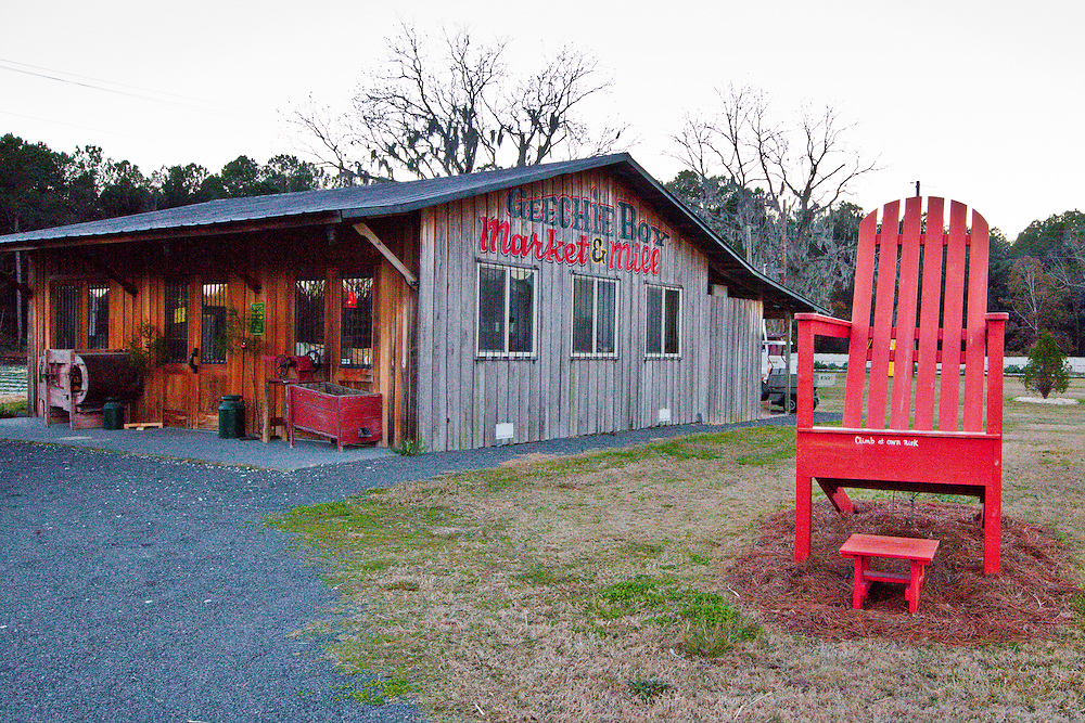A large red chair sits outside Geechie Boy Market and Mill on Edisto Island South Carolina.
