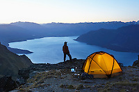 Man looking at lake next to tent at dusk