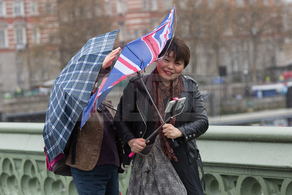 © Licensed to London News Pictures. 15/04/2016. London, UK. Tourists struggle with their umbrella whilst taking a selfie during heavy rain showers in central London during wet and windy weather today. Photo credit : Vickie Flores/LNP
