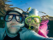 "Snorkelers: man & woman selfie in rippled water. We kayaked on a Kona Boys tour to the Captain Cook Monument in Kealakekua Bay State Historical Park starting from Napoopoo Pier, on the Kona Coast of the Big Island, Hawaii, USA. With one of the most pristine coral reefs for snorkeling in the state, Kealakekua Bay is protected as a State Marine Life Conservation District (MLCD). British Captain James Cook was the first European to reach the Hawaiian islands (in January 1778 at Waimea harbour on Kauai), and he named the archipelago the ""Sandwich Islands."" During his second voyage to the Hawaiian Islands, Captain Cook arrived at Kealakekua Bay in 1779. Thought by the natives to be a god, due to his arrival during a celebration and time of peace for Lono, Cook was treated royally. But the following month he was killed in a skirmish on the shores of Ka'awaloa Cove following a series of incidents between his crew and the Hawaiians. In 1874, the 27-foot monument was erected nearby in Cook's honor by his countrymen. On the lava flats behind Cook Monument are the ruins of the ancient village of Ka'awaloa. For this photo's licensing options, please inquire."