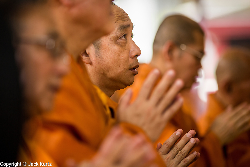 12 DECEMBER 2013 - BANGKOK, THAILAND: Thai-Chinese Mahayana Buddhist Monks participate a chanting service during a mourning service for the Supreme Patriarch of Thailand in a  at Wat Bowon Niwet in Bangkok. Somdet Phra Nyanasamvara, who headed Thailand's order of Buddhist monks for more than two decades and was known as the Supreme Patriarch, died Oct. 24 at a hospital in Bangkok. He was 100. He was ordained as a Buddhist monk in 1933 and rose through the monastic ranks to become the Supreme Patriarch in 1989. He was the spiritual advisor to Bhumibol Adulyadej, the King of Thailand when the King served as monk in 1956. There is a 100 day mourning period for the Patriarch, the service Thursday, on the 50th day, included members of the Thai Royal Family. Although the Patriarch was a Theravada Buddhist, he was the Supreme Patriarch of all Buddhists in Thailand, including the Mahayana sect, which is based in Chinese Buddhism.     PHOTO BY JACK KURTZ