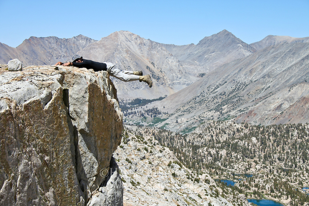 Hiker hanging out over a cliff ledge overlooking Sixty Lakes Basin, Kings Canyon National Park