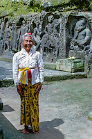 Bali, Gianyar, Yeh Pulu. A Pemangku, a holy old woman who watches over and maintains the site. Behind her the statue of Ganesh with the elephant head.
