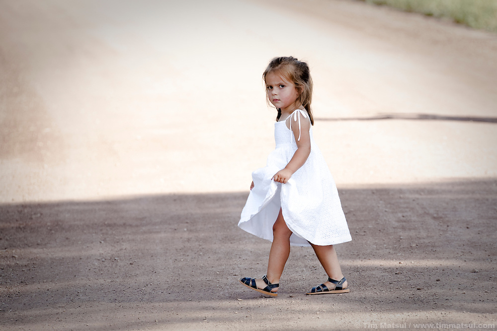 A five year-old girl in a white sundress crosses a dirt road and stares with a scowl.