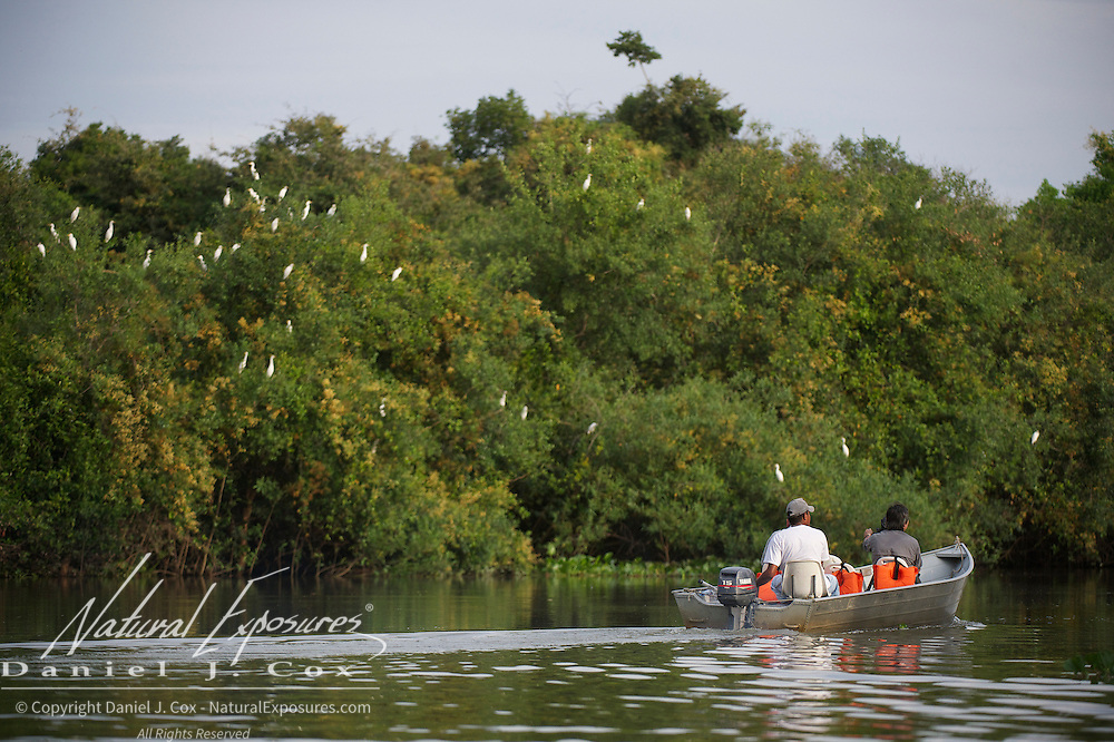 A small boat with tourists on the Rio Pixaim River, Pantanal, Brazil.