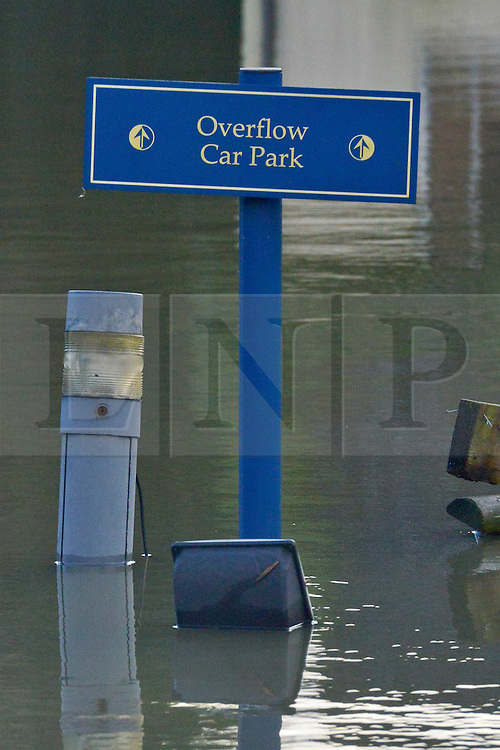 """© Licensed to London News Pictures. 09/01/2014. Marlow, UK. A sign at a car park saying """"Overflow Car Park"""" stands in floodwater. Rising river levels in the River Thames at Marlow in Buckinghamshire have led to flooding and property damage along the river today 9th January 2014. Large areas of Britain are experiencing flooding after wet weather. Photo credit : Stephen Simpson/LNP"""