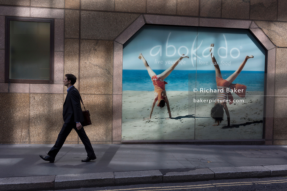 A businessman walks past a business window of healthfood and coffee retailer Abokado, on 26th June, in the City of London, England. Abokado is a fast food chain based in the United Kingdom, founded by Mark Lilley and his wife Lindsay in 2004, with the first store opening in London's Covent Garden.
