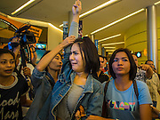 20 NOVEMBER 2014 - BANGKOK, THAILAND:  NATCHACAH KONG-UDOM grimaces while plainclothes female Thai police officers lead her away for speaking out against the coup and displaying the three fingered salute from the Hunger Games movies. Kong-Udom was one of at least three people arrested by Thai police during the opening the Hunger Games: Mockingjay - Part 1 in Bangkok Thursday. Opponents of the Thai military coup have adapted the three fingered salute used in the Hunger Games series as a sign of their opposition to the coup. In the weeks before the movie opening Thai police arrested several people for using the Hunger Games salute and Thai media reported that one Thai movie theater chain cancelled plans to show the movie at the request of the military government. There were several small protests at theaters showing the movie Thursday.    PHOTO BY JACK KURTZ