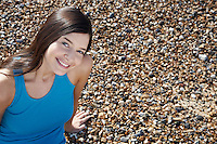 Young woman smiling sitting on beach portrait elevated view