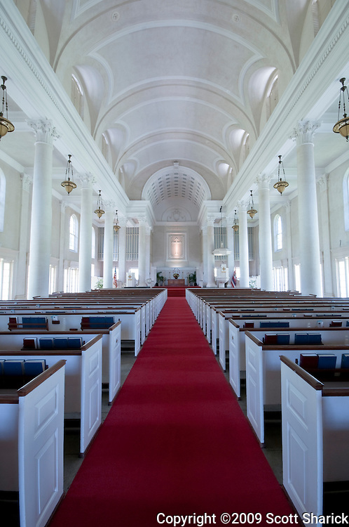 A red carpet leads the way down the aisle of an old church with a white interior.
