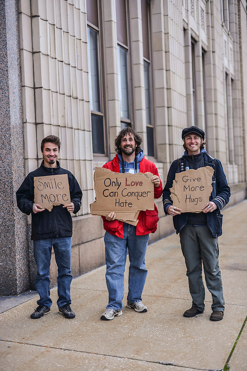 Artists outside Summit Artspace during Akron Art Prize 2014 holding cardboard signs with positive messages.