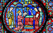 Emperor Charlemagne, 742-814, kneels before the altar at the imperial chapel at Aix-la-Chapelle, handing a relic, possibly the crown of thorns, to the abbot. Roland accompanies him, on the left. Medallion of Charlemagne donating his relics at Aix-la-Chapelle, from the Charlemagne window, early 13th century, in the ambulatory of Chartres Cathedral, Eure-et-Loir, France. Chartres cathedral was built 1194-1250 and is a fine example of Gothic architecture. Most of its windows date from 1205-40 although a few earlier 12th century examples are also intact. It was declared a UNESCO World Heritage Site in 1979. Picture by Manuel Cohen
