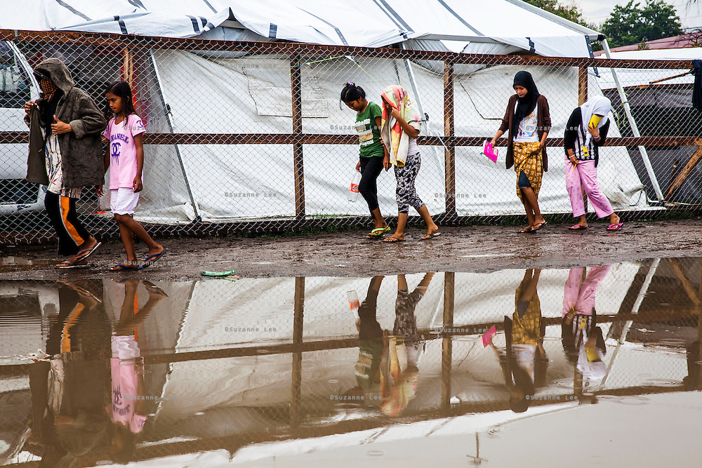 Survivors of the Zamboanga City rebel attack walk in pairs after visiting the restrooms of the evacuation center in the city's largest stadium in Zamboanga, Mindanao, The Philippines on November 5, 2013. SPRINT-IPPF's partner NGO FPOP has advocated and implemented gender segregated restrooms to try to reduce gender based violence cases such as rape in the IDP camps. Photo by Suzanne Lee for SPRINT-IPPF