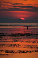 Red rising sun reflected in the ocean at Sanur Beach in Bali, Indonesia