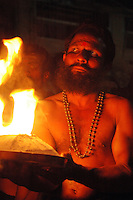 India, Karnataka, Gokarna, 2006. A Keralan Hindu priest carries the symbolic birth fire backwards for over five miles to initiate the evening's prayers.