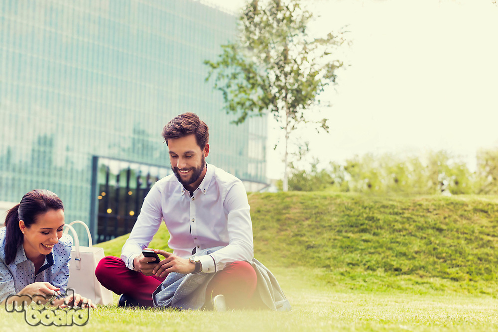 Business people using smartphone while sitting on the grass