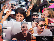 07 JULY 2015 - BANGKOK, THAILAND: Activists rally at the Ministry of Defense and hold photos of the 14 students arrested by the military. About 100 people gathered in front of the Ministry of Defense in Bangkok Tuesday to support 14 university students arrested two weeks ago for violating orders against political assembly. They're facing criminal trial in military courts. The courts ordered their release Tuesday because they can only be held for two weeks without trial, the two weeks expired Tuesday and the military court chose not to renew their pretrial detention. The court order was not an acquittal. They still face trial and possible prison sentences if convicted.        PHOTO BY JACK KURTZ