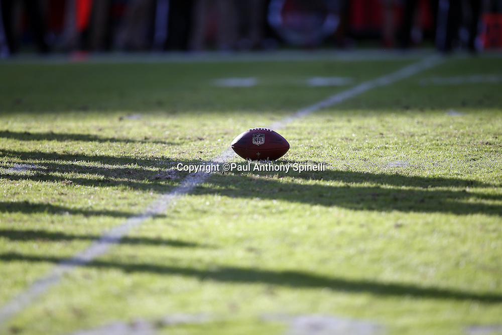A football lies on the grass as long shadows cover the field during a break in the action at the Tampa Bay Buccaneers 2015 week 14 regular season NFL football game against the New Orleans Saints on Sunday, Dec. 13, 2015 in Tampa, Fla. The Saints won the game 24-17. (©Paul Anthony Spinelli)