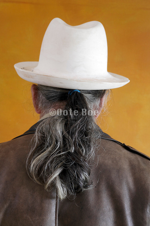 man with ponytail wearing a white plaster fedora hat