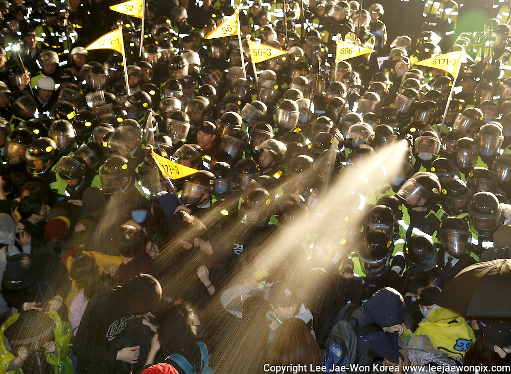 Policemen use pepper spray to protesters trying to march toward Gwanghwamun gate near the presidential Blue House in Seoul, April 18, 2015. About 30,000 people (8,000 people by police estimate) demonstrated on April 18, two days after the first anniversary of Sewol ferry tragedy to demand that the government hold a thorough investigation into the tragedy and President Park Geun-Hye resign. The police detained about 100 people during the protest. Photo by Lee Jae-Won (SOUTH KOREA) www.leejaewonpix.com/