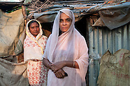 A woman and her sister pose for a portrait outside their home in Ward 11, Chittagong, Bangladesh.