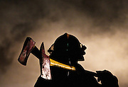 A firefighter's axes are illuminated by a work light at the scene of a barn fire at 606 W. 14 Road near Phillips. The barn had not been used since a tornado in 1980 which moved it from its foundation according to owner Dennis Comer. Firefighters from Phillips and Aurora were dispatched around 8:13 p.m. Mutual aid with tankers and manpower was called for by radio about 10 minutes later and Giltner responded.