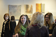 "Roslyn, New York, USA. January 31, 2015. Ellen Hallie Schiff, at extreme right, speaks with visitors at Artists Reception for ""The Alchemists"" at Bryant Library. Schiff curated the exhibition, which included artwork of five artists, including herself."