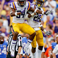 Oct 12, 2013; Baton Rouge, LA, USA; LSU Tigers safety Micah Eugene (34) and LSU Tigers cornerback Jalen Mills (28) celebrate a defensive stop during the second half of a game after the game at Tiger Stadium. LSU defeated Florida 17-6. Mandatory Credit: Derick E. Hingle-USA TODAY Sports