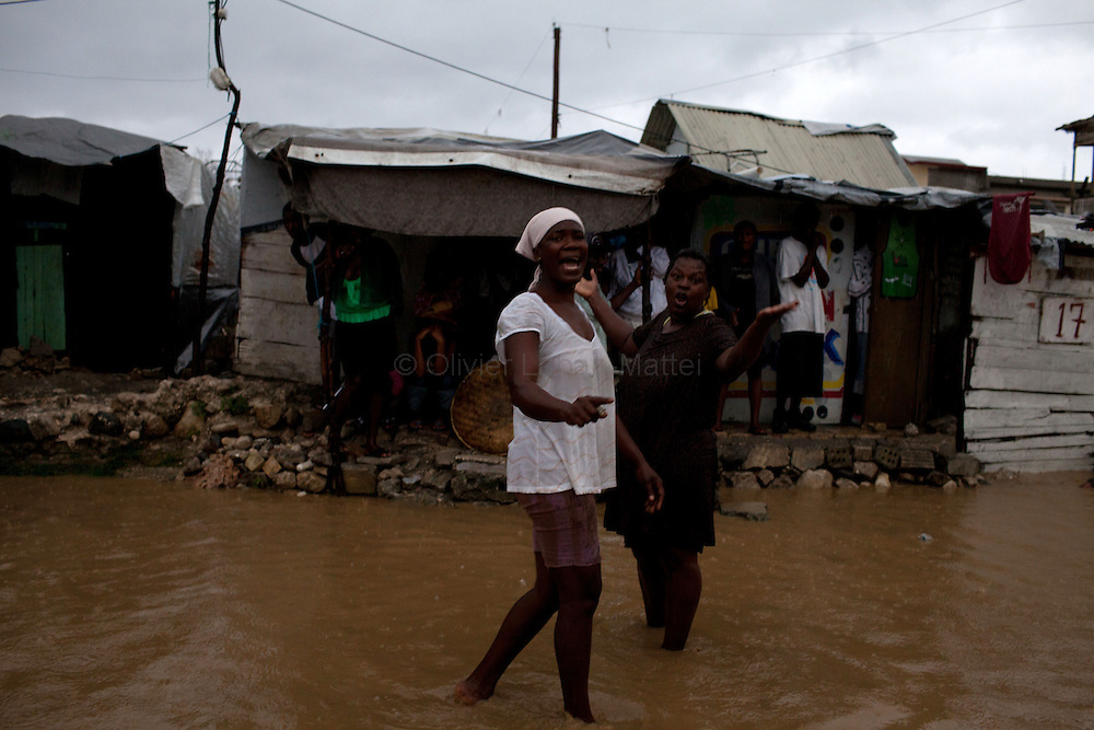After hurricane Tomas went through Haiti, the city of Leogane has been totally flooded by the heavy rain and the overflow of the river Roullorne.///Haitian women stand before their house, in a street of Leogane full of muddy water, during hurricane Tomas.