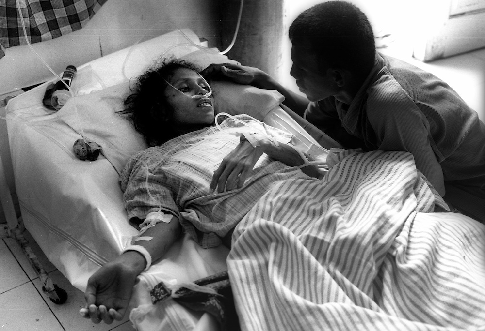 A man comforts his wife at Farikinah Hospital, a victim of the devastating Tsunami that destroyed most of Banda Aceh.