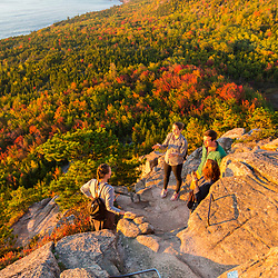 "Hikers take a break on ""The Beehive"" in fall in Maine's Acadia National Park."