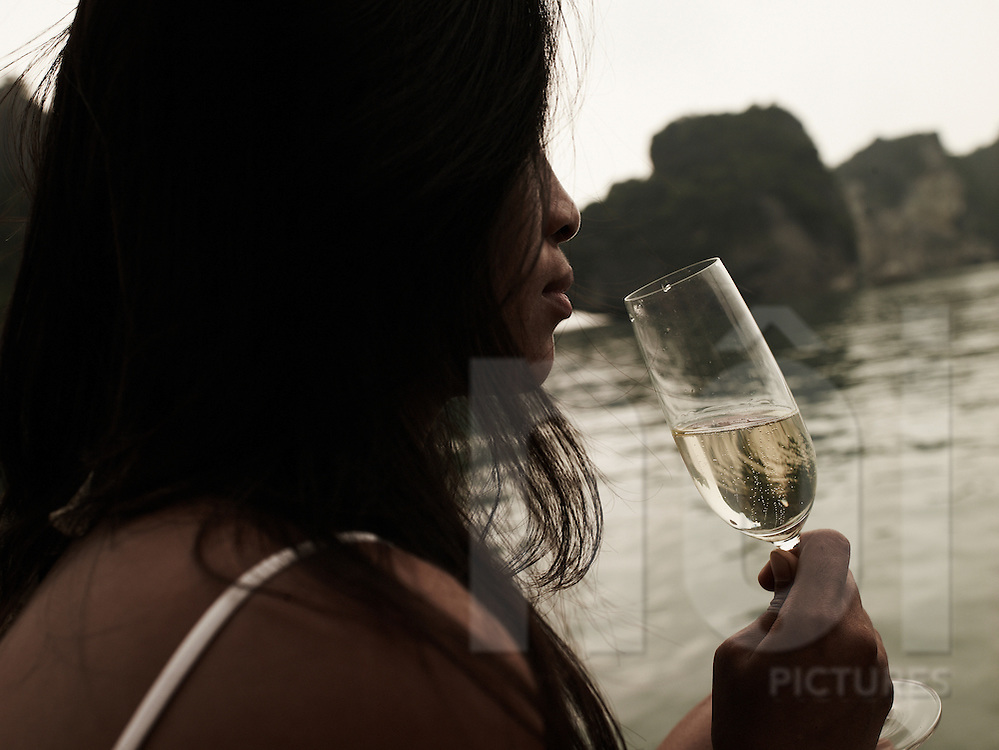 A vietnamese woman drinks champagne and enjoys seascape of Ha Long bay, a UNESCO world heritage site, Vietnam, Asia