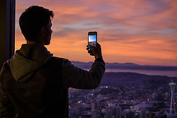 North America, United States, Washington, Seattle. A young man takes a photo with a smartphone, overlooking Puget Sound at sunset.