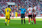 Kwesi Appiah (#9) of AFC Wimbledon is booked for diving in the box by referee Anthony Backhouse during the EFL Sky Bet League 1 match between Sunderland and AFC Wimbledon at the Stadium Of Light, Sunderland, England on 24 August 2019.